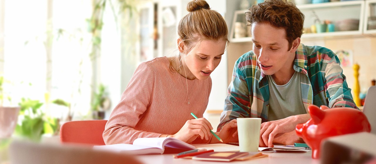 Zwei junge Leute sitzen mit Unterlagen am Tisch.